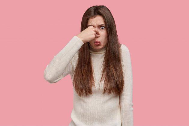 žena s hnedými vlasmi si zapcháva nos rukou pretože cíti zápach z penisu